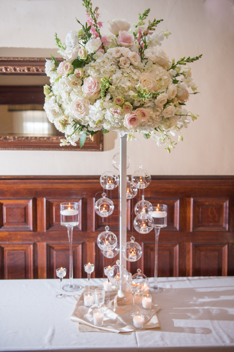 white floral arrangement in a high vase with hanging glass globes for votive candles