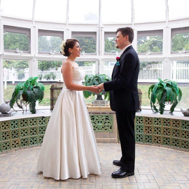 rachel-and-robert-holdiing-hands-in-glass-conservatory-cuban-theme-wedding