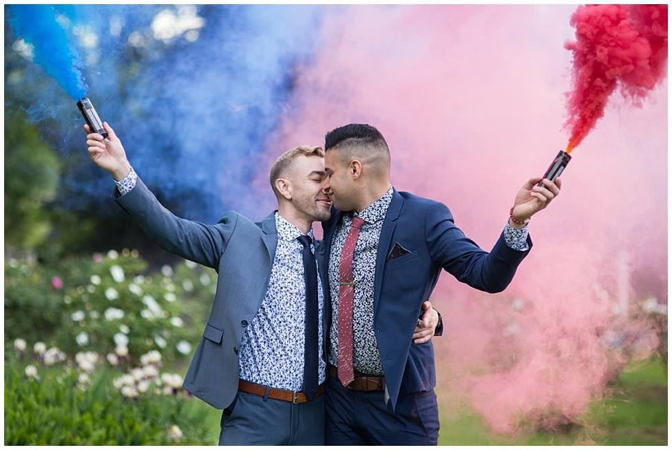 couple facing each other outside with colored smoke streamers