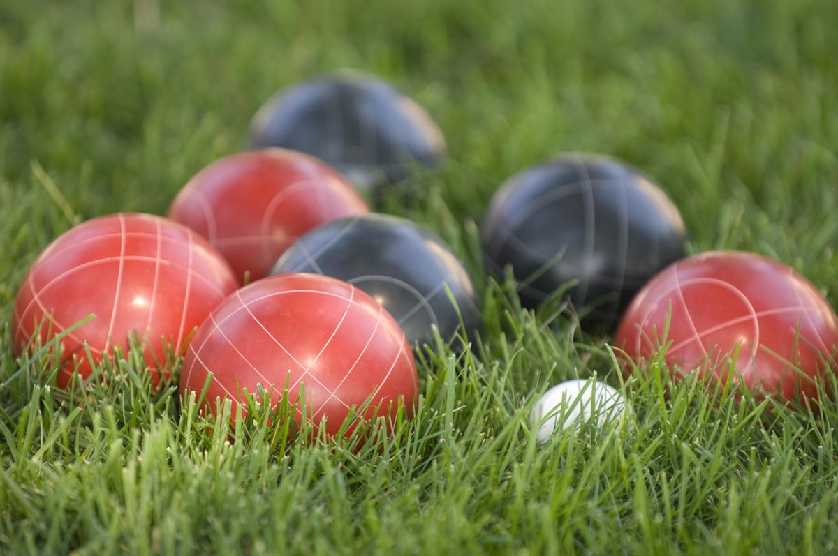 blue and red bocce balls in grass