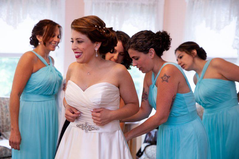 cuban-flair-wedding-Four-bridesmaids-in-aqua-helping-Rachel-into-her-gown