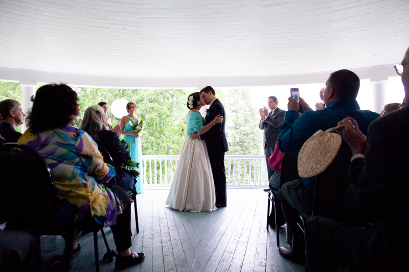cuban-flair-wedding-newlywed-couple-share-their-first-kiss-on-veranda-in-front-of-guests