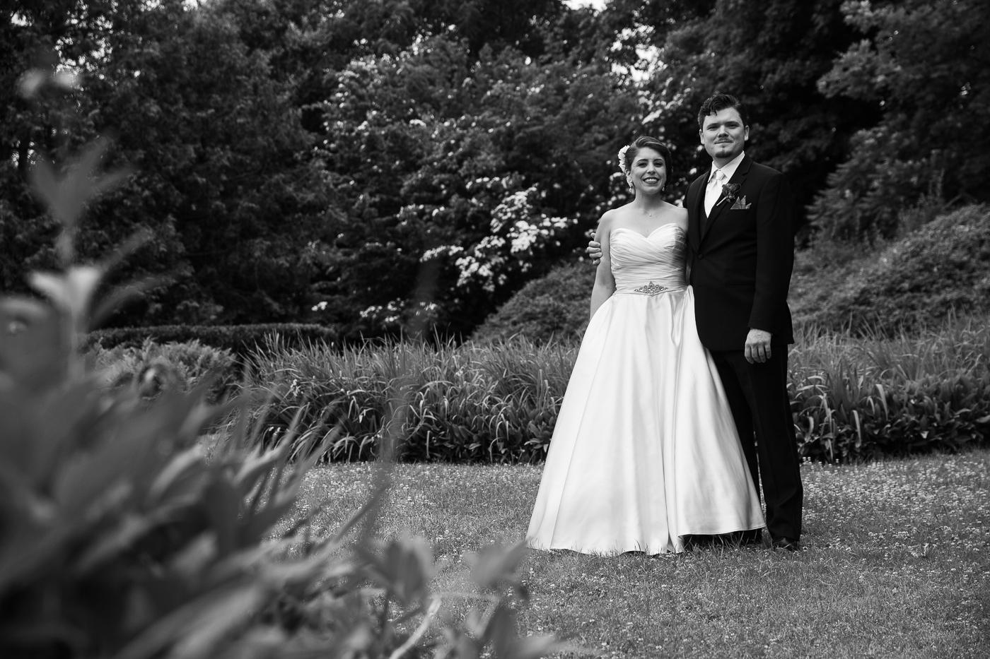 bride and groom posing in flower garden