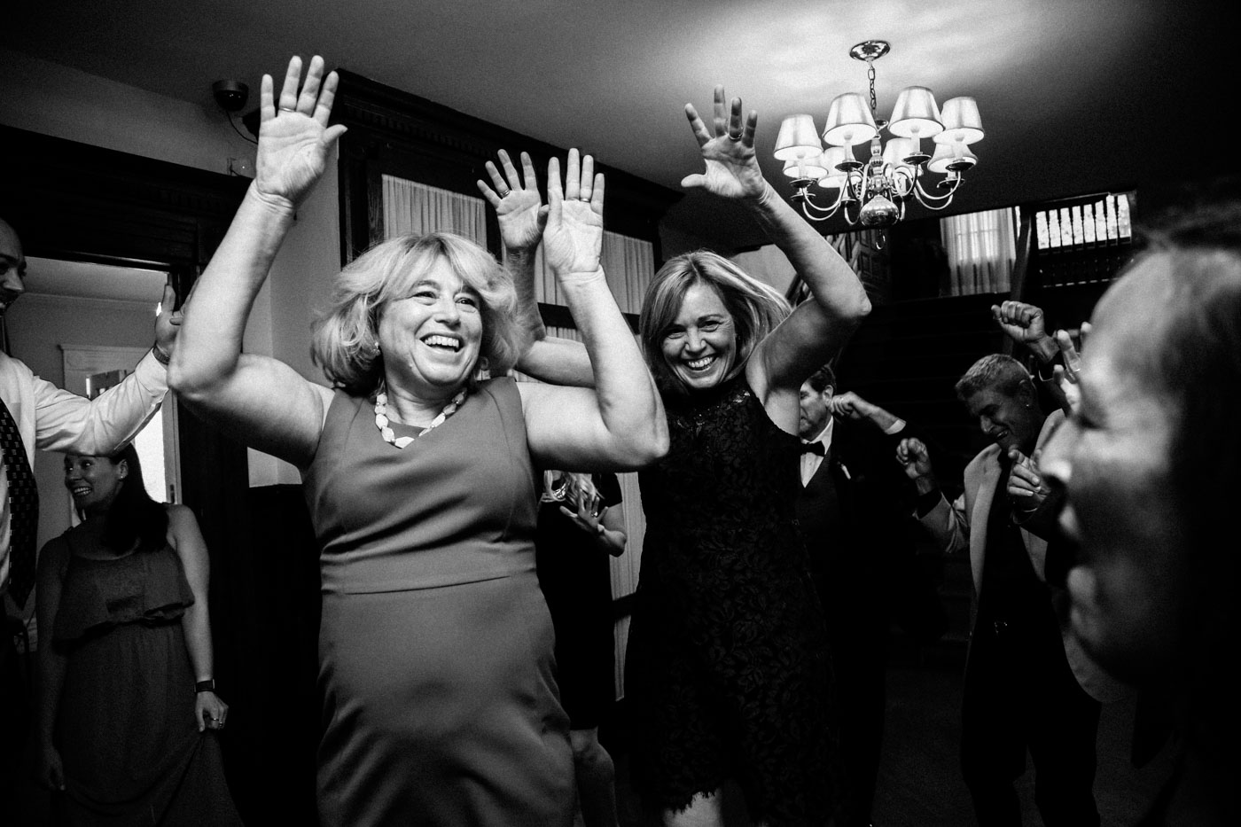 two women dancing with hands in air at wedding