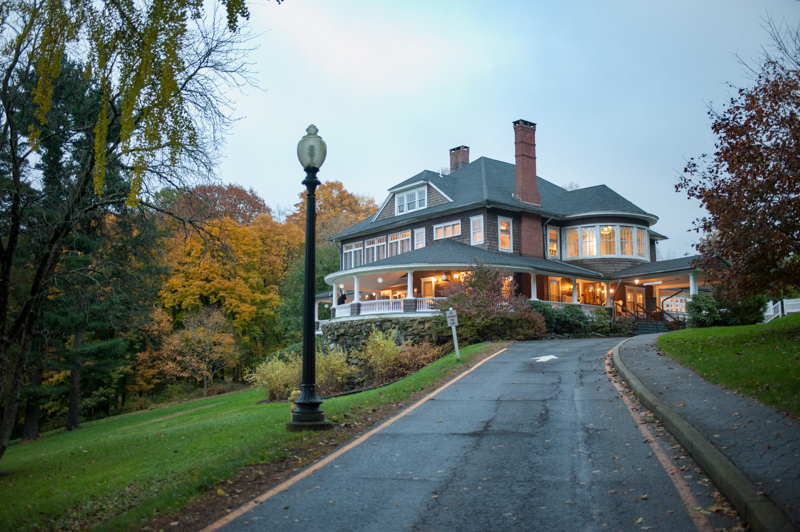 the mansion lit up surrounded by fall foliage at dusk