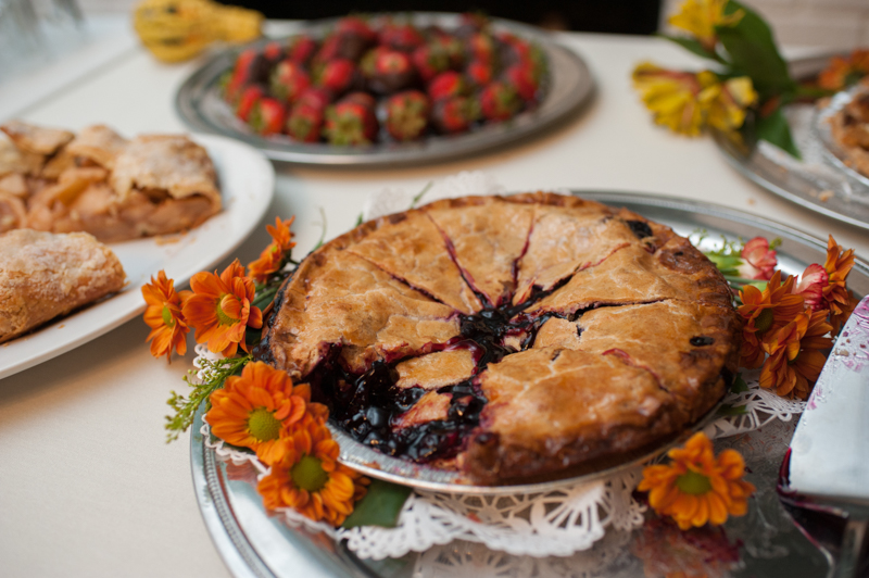 blueberry pie and chocolate covered strawberries on the table