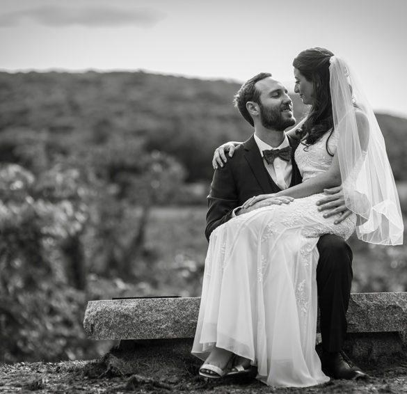 bride sitting on grooms lap overlooking hayfields