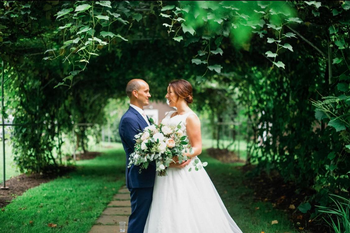 bride and groom facing each other under the grape arbor