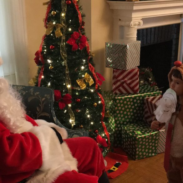 child in rudolf costume talking to santa