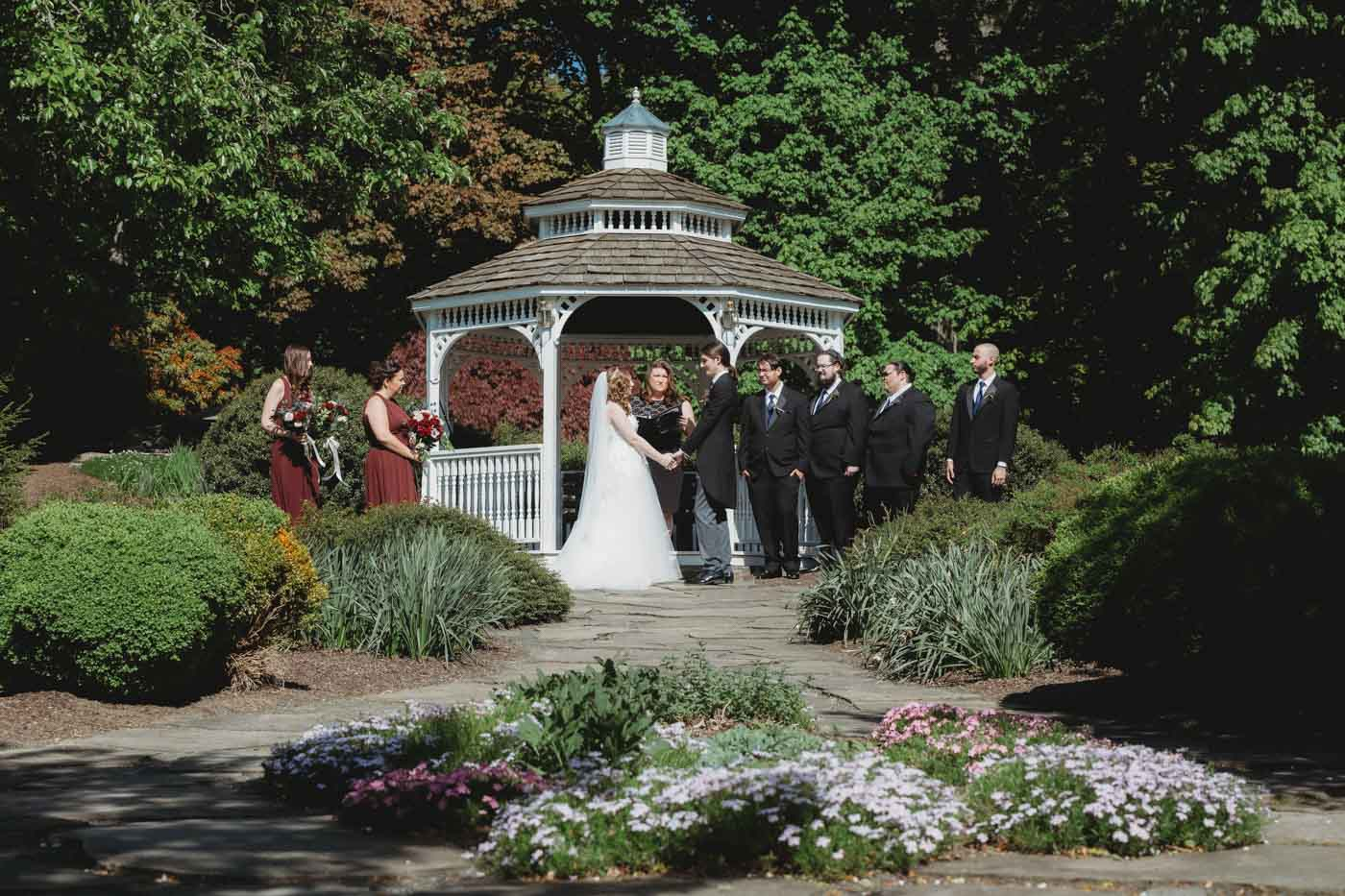 gazebo-wedding-couple-exchanging-vows-before-guests