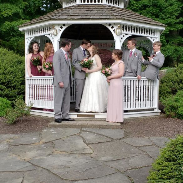 couple kissing in gazebo surrounded by wedding part