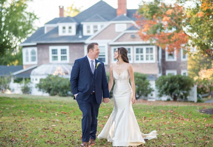 bride-groom-hand-in-hand-across-lawn-with-mansion-in-background