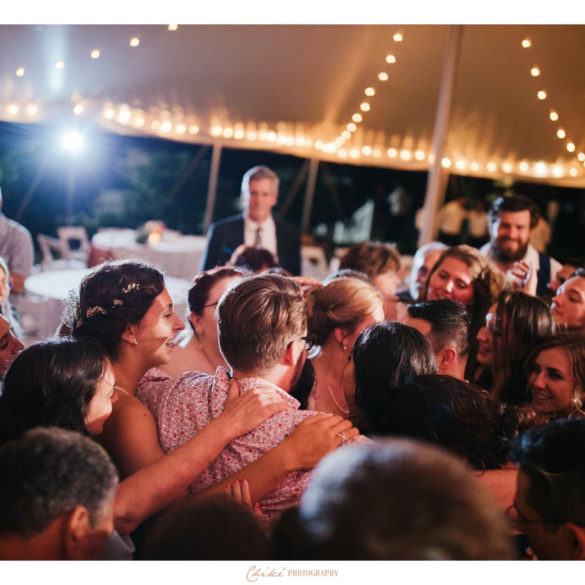 college grads surrounded by family on dance floor