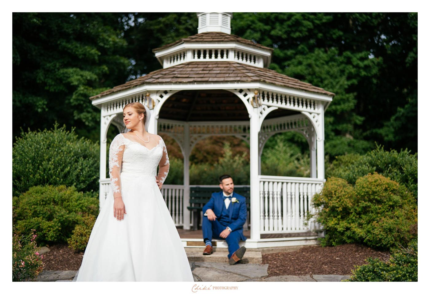 groom sitting on gazebo steps with bride in front