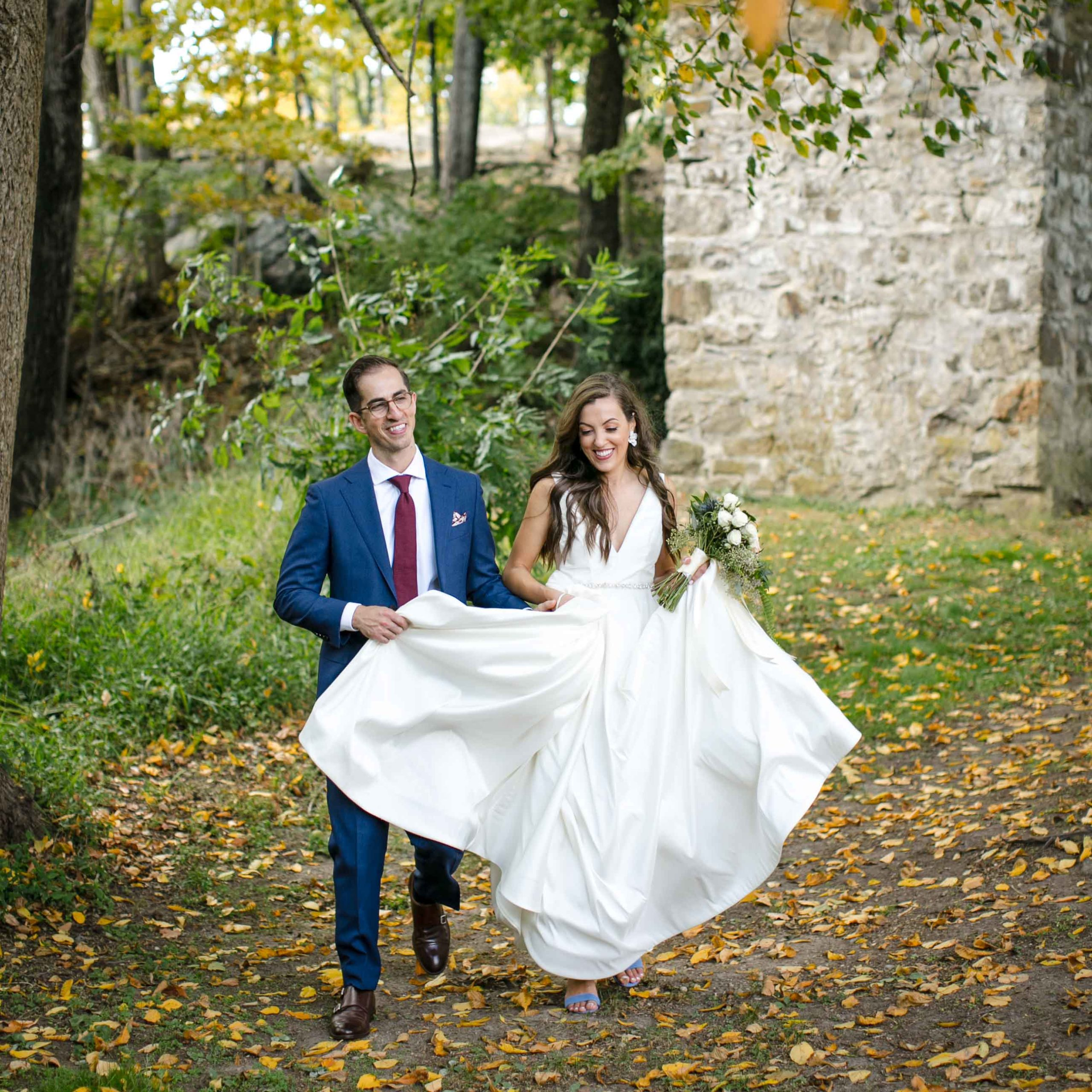 bride and groom walking on leaf strewn lawn