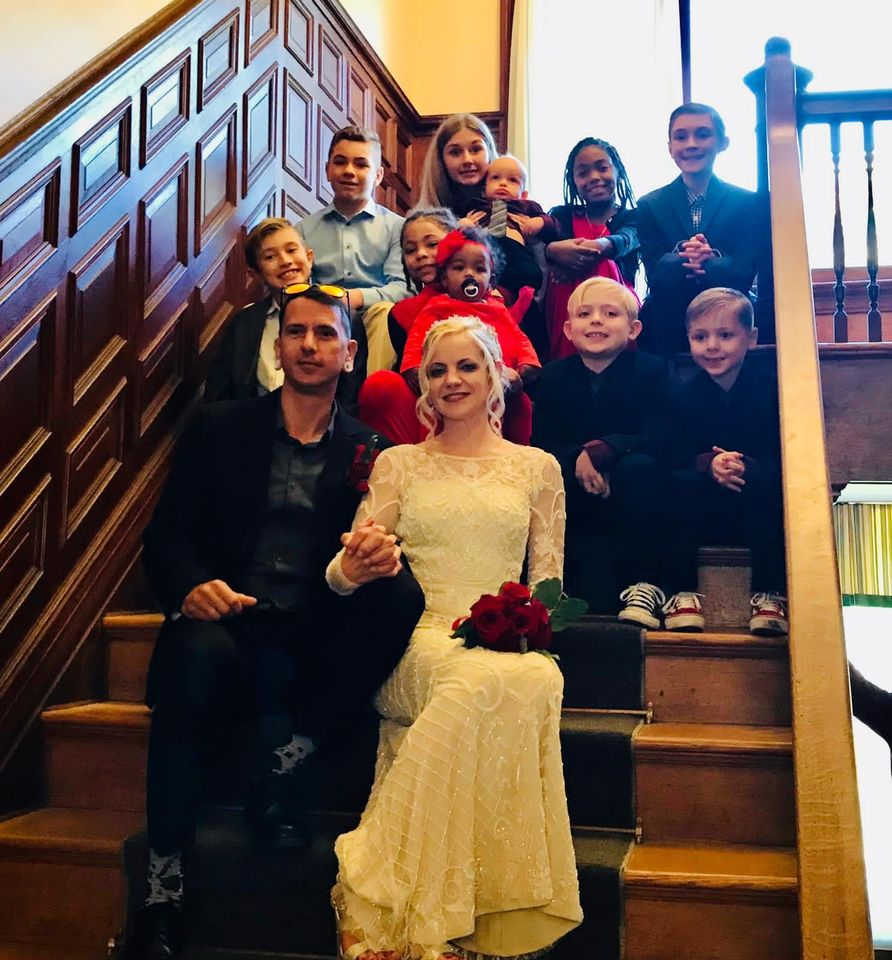 julia and greg on stairs surrounded by children