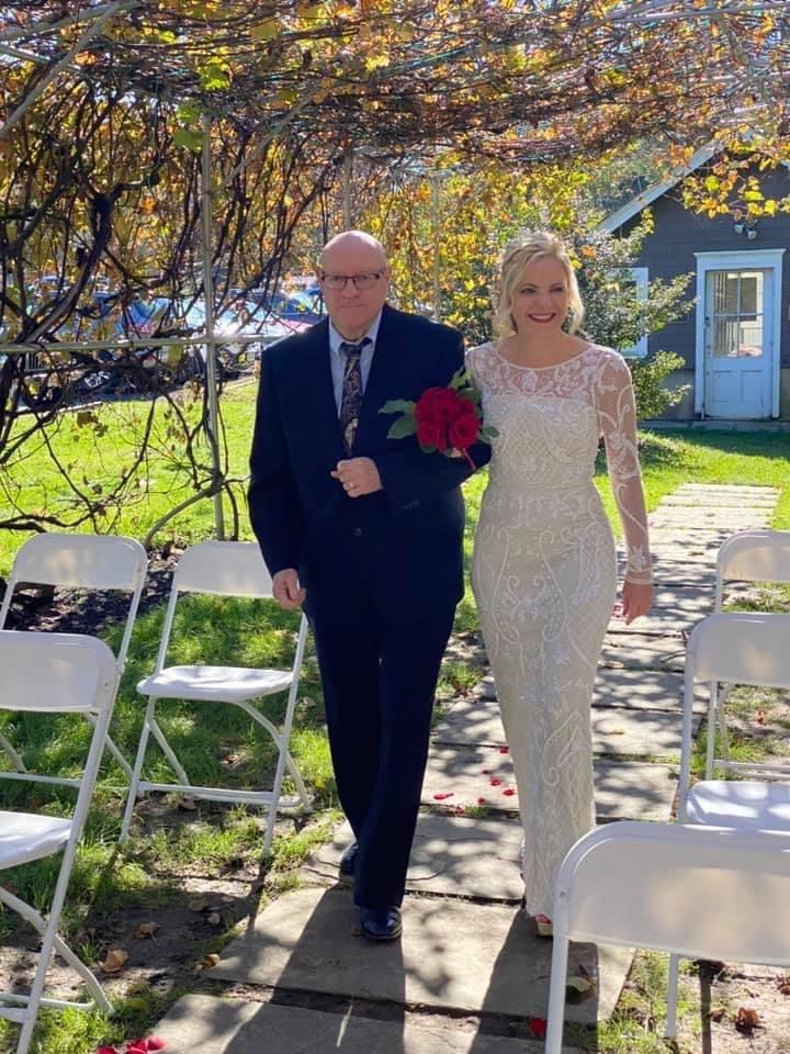julia and dad walking arm in arm under grape arbor
