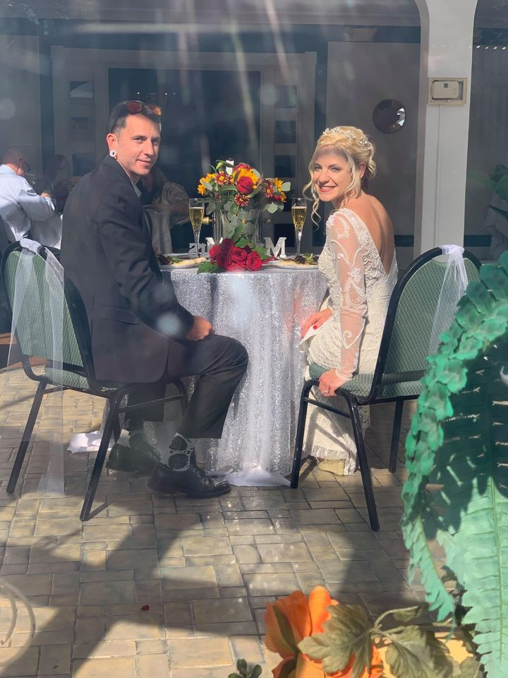 couple seen througj window at sweetheart table