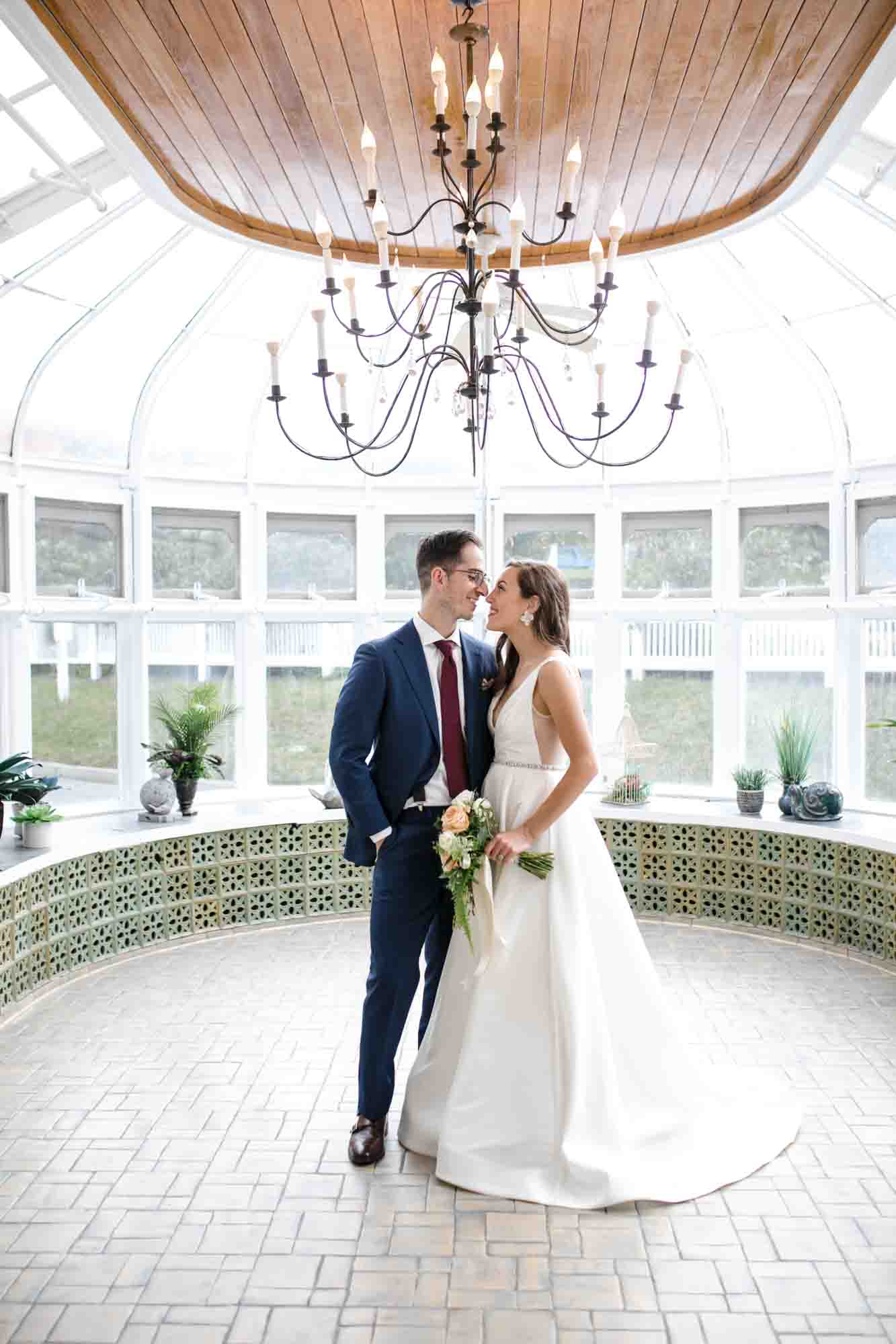 bride and groom standing close in glass conservatory