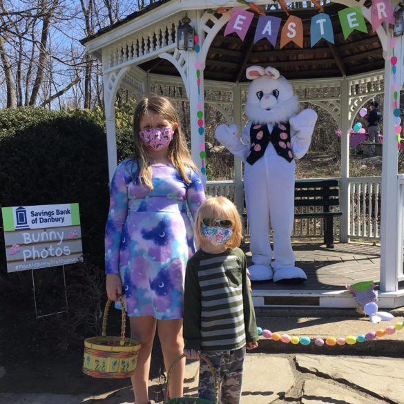 girl and boy standing in front of easter bunny